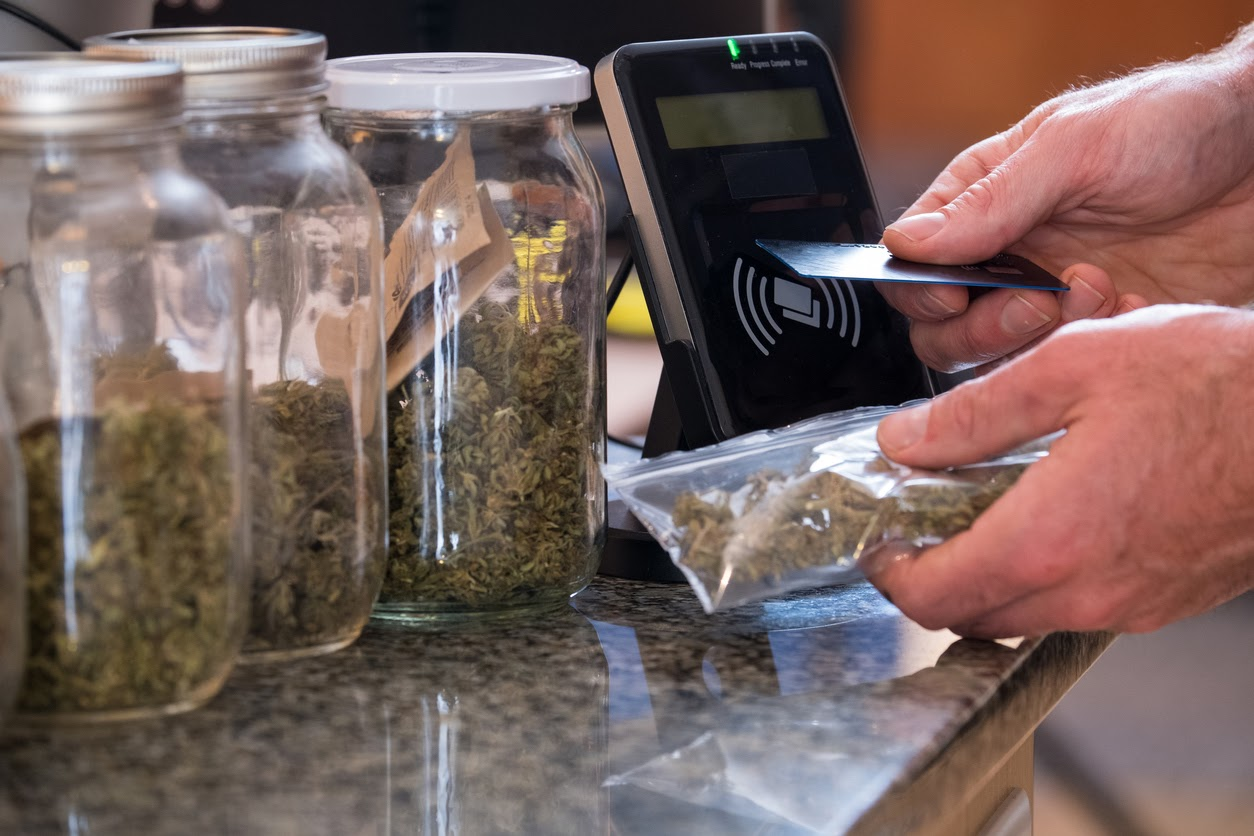 A medical marijuana patient purchases dried flower in a bag